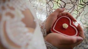 Mooie vrouwen` s handen die hart gevormde verlovingsringdoos houden Bruid die een hart gevormde giftdoos in haar handen houden stock footage