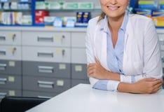 Mooie vrouwenapotheker die zich bij haar werkplaats in apotheek bevinden Stock Foto's