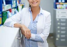Mooie vrouwenapotheker die zich bij haar werkplaats in apotheek bevinden royalty-vrije stock foto's