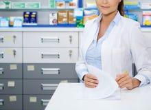 Mooie vrouwenapotheker die zich bij haar werkplaats in apotheek bevinden royalty-vrije stock afbeelding