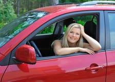 Mooie vrouwenbestuurder in rode glanzende auto in openlucht stock fotografie