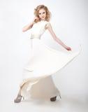 Mooie vrouwenblonde in vliegende lente witte dres Royalty-vrije Stock Foto's