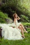 Mooie vrouwenbruid die met lange benen in aard genieten van Royalty-vrije Stock Afbeeldingen