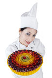 Mooie vrouwenchef-kok die een cake houden Royalty-vrije Stock Afbeelding