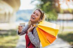 Mooie vrouwenholding het winkelen zakken en een creditcard royalty-vrije stock foto's