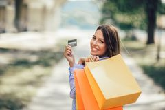Mooie vrouwenholding het winkelen zakken en een creditcard stock fotografie