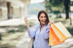 Mooie vrouwenholding het winkelen zakken en een creditcard royalty-vrije stock foto