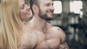 Mooie vrouwenkussen achter het oor, de bodybuilder en zij glimlachen stock video