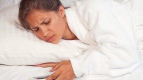 Mooie vrouwenontwaken om wekker op haar smartphone uit te zetten stock videobeelden