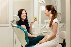 Mooie vrouwenpati?nt die tandbehandeling hebben op tandarts` s kantoor De glimlachende vrouw houdt een appel stock foto