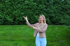 Mooie vrouwenpunten met beide handen op potentiële plaats aan adv royalty-vrije stock foto's