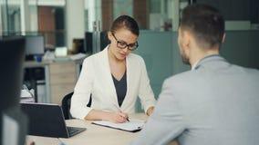 Mooie vrouwenrecruiter spreekt aan mannelijke kandidaat tijdens baaninterviewer in bureau, neemt het meisje nota's die dan schudd stock video
