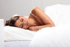 Mooie vrouwenslaap in bed in het kader van witte bladen stock foto
