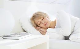 Mooie vrouwenslaap in wit bed Stock Afbeelding