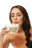 Mooie vrouwenslag aan haar hete cappuccino's Stock Foto's