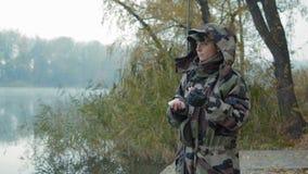 Mooie vrouwenvisser in camouflage en leerhandschoenen een hengel houden en lokmiddel die voor vissen stock video