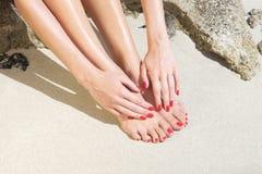Mooie vrouwenvoeten met rode manicure en pedicure: het ontspannen op zand Royalty-vrije Stock Fotografie
