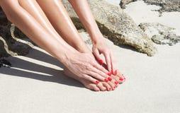 Mooie vrouwenvoeten met rode manicure en pedicure: het ontspannen op zand Royalty-vrije Stock Foto