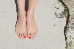 Mooie vrouwenvoeten met rode pedicure: het ontspannen op zand Royalty-vrije Stock Fotografie