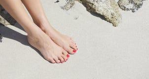 Mooie vrouwenvoeten met rode pedicure: het ontspannen op zand Stock Afbeeldingen