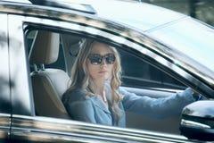 mooie vrouwenzitting in auto Stock Afbeelding