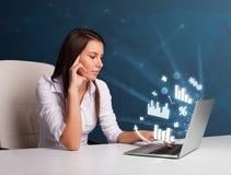 Mooie vrouwenzitting bij bureau en het typen op laptop met diagrammen Stock Fotografie
