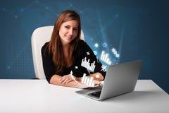 Mooie vrouwenzitting bij bureau en het typen op laptop met diagrammen Royalty-vrije Stock Foto's