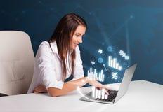 Mooie vrouwenzitting bij bureau en het typen op laptop met diagrammen Stock Afbeelding