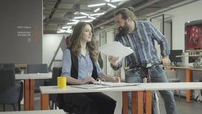 Mooie vrouwenzitting bij haar werkplaats in het bureau die haar werk doen De gebaarde glimlachende mens berijdt dichter zijn fiet stock video