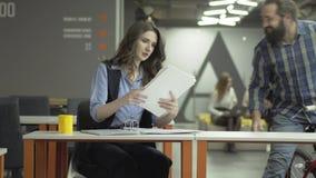 Mooie vrouwenzitting bij haar werkplaats in het bureau die haar werk doen De gebaarde positieve mens berijdt dichter zijn fiets m stock videobeelden