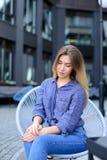 Mooie vrouwenzitting bij koffie die buiten en blauw overhemd dragen Stock Afbeeldingen