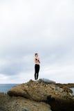 Mooie vrouwenzitting bovenop een rots en het mediteren Royalty-vrije Stock Fotografie