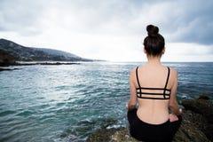 Mooie vrouwenzitting bovenop een rots en het mediteren Stock Foto