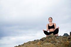 Mooie vrouwenzitting bovenop een rots en het mediteren Royalty-vrije Stock Foto's