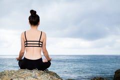 Mooie vrouwenzitting bovenop een rots en het mediteren Stock Afbeeldingen