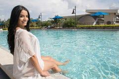 Mooie vrouwenzitting door de pool Stock Afbeeldingen