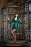 Mooie vrouwenzitting in een kooi alleen wegens haar beperkingen en complexen volwassen wijfje die groene avondjurk binnen dragen royalty-vrije stock foto