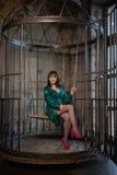 Mooie vrouwenzitting in een kooi alleen wegens haar beperkingen en complexen volwassen wijfje die groene avondjurk binnen dragen stock foto