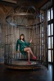 Mooie vrouwenzitting in een kooi alleen wegens haar beperkingen en complexen volwassen wijfje die groene avondjurk binnen dragen stock foto's