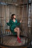 Mooie vrouwenzitting in een kooi alleen wegens haar beperkingen en complexen volwassen wijfje die groene avondjurk binnen dragen royalty-vrije stock fotografie