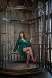 Mooie vrouwenzitting in een kooi alleen wegens haar beperkingen en complexen volwassen wijfje die groene avondjurk binnen dragen stock afbeelding