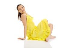 Mooie vrouwenzitting in gele kleding Stock Foto's