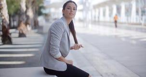 Mooie vrouwenzitting naast een voetgang royalty-vrije stock afbeelding