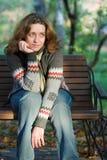 Mooie vrouwenzitting op een bank in park Stock Foto's