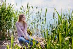 Mooie vrouwenzitting op een pijler bij het meer Stock Afbeelding
