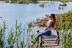 Mooie vrouwenzitting op een pijler bij het meer Royalty-vrije Stock Foto's