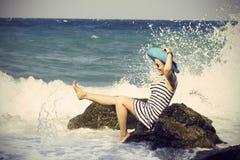 Mooie vrouwenzitting op een steen en het bespatten Stock Foto's