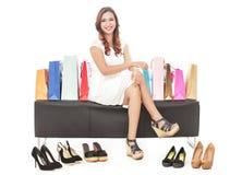 Mooie vrouwenzitting tussen het winkelen zakken en paren schoenen Royalty-vrije Stock Afbeeldingen