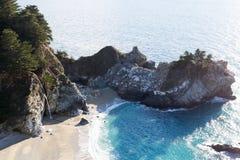 Mooie Waterval die op Zand naast Oceaan landen Stock Foto