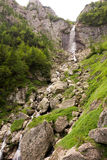 Mooie waterval op een rotsachtige vallei met verspreide vegetatie Royalty-vrije Stock Fotografie